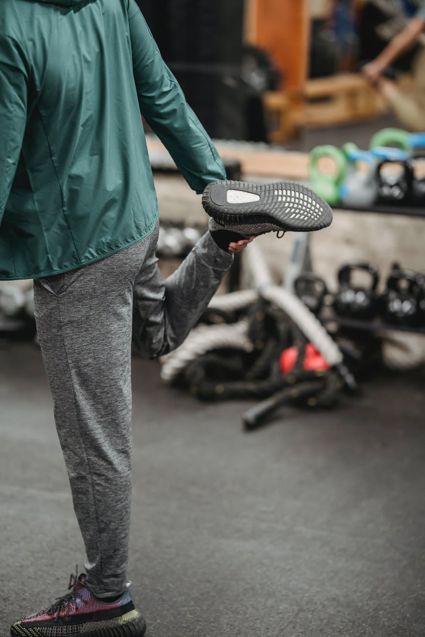 crop unrecognizable sportsman stretching leg in gym